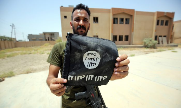 A member of the Iraqi pro-government forces holds an upside down Islamic State (ISIS) flag after recapturing the city from the jihadists in a street in Fallujah on June 30, 2016 (Ahmad al-Rubaye/AFP/Getty Images)
