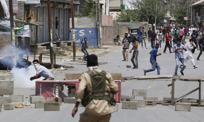 A masked Kashmiri protester prepares to throws a brick at an Indian policeman during a protest in Srinagar, Indian controlled Kashmir, on July 9, 2016. Indian authorities imposed an indefinite curfew in most parts of Kashmir on Saturday, a day after government forces killed the top rebel commander in the disputed Himalayan region, officials said, describing it as a major success against rebels fighting Indian rule. (AP Photo/Mukhtar Khan)