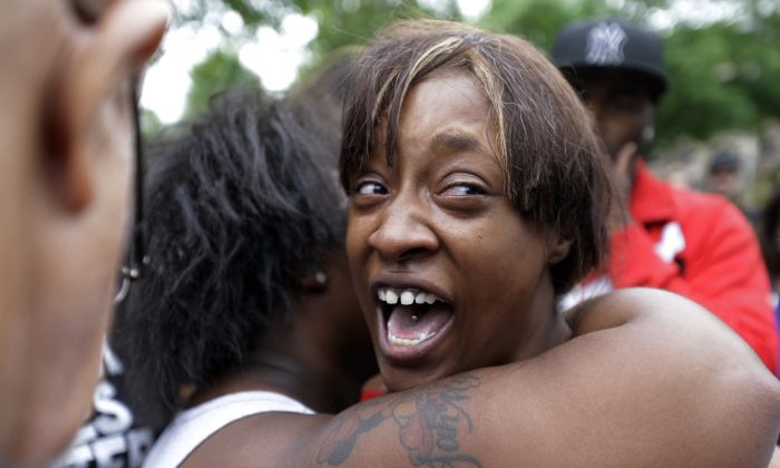 Diamond Reynolds, the girlfriend of Philando Castile, is consoled as she talks about his shooting death with protesters and media outside the governor's residence in St. Paul, Minn. (AP Photo/Jim Mone)