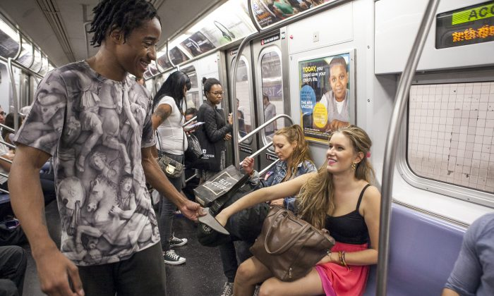 Ainsley Brundage, a subway acrobat, collects money after his performance on the subway in New York. (Samira Bouaou/Epoch Times)