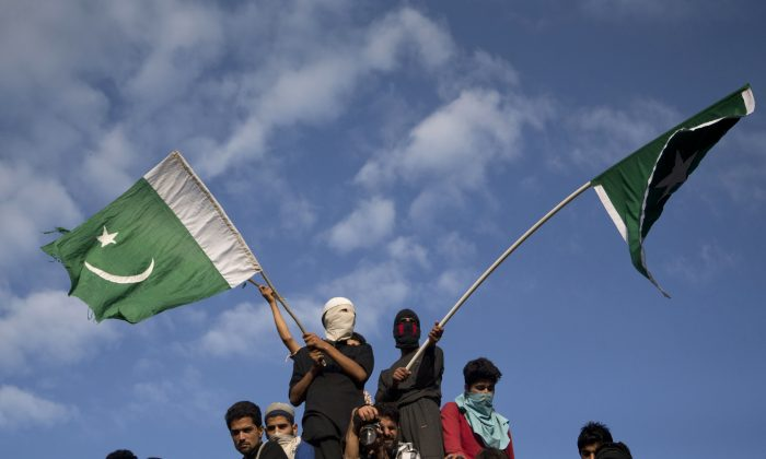 Kashmiri villagers wave Pakistani flags during the funeral procession of Burhan Wani, chief of operations of Indian Kashmir's largest rebel group Hizbul Mujahideen, in Tral, some 24 miles south of Srinagar, Indian controlled Kashmir, on July 9, 2016. Indian troops fired on protesters in Kashmir as tens of thousands of Kashmiris defied a curfew imposed in most parts of the troubled region Saturday and participated in the funeral of the top rebel commander killed by Indian government forces, officials and locals said. (AP Photo/Dar Yasin)
