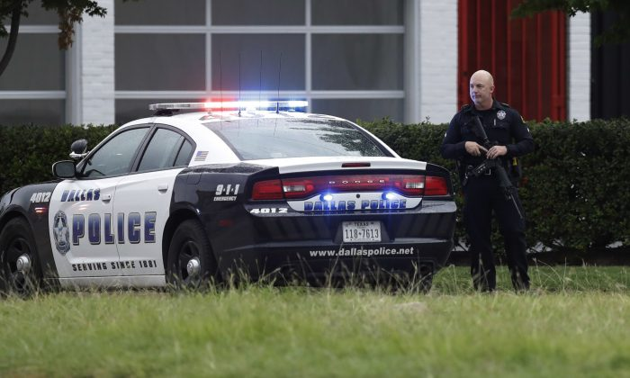 Dallas police tighten security at their headquarters after receiving an anonymous threat against law enforcement across the city on July 9, 2016. Security measures were heightened after a peaceful protest, over the recent shootings of black men by police, turned violent Thursday night when gunman Micah Johnson shot at officers, killing several and injuring others. (AP Photo/Eric Gay)