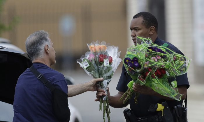 A Dallas police officer receivers flowers at a roadblock outside their headquarters in Dallas on July 9, 2016. (AP Photo/Eric Gay)