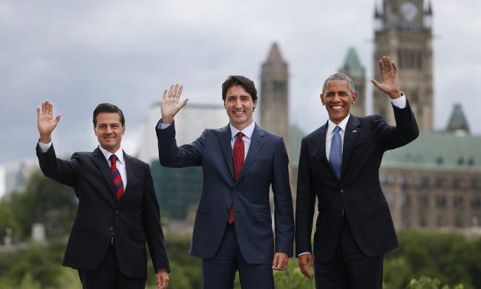 (L-R) Mexican President Enrique Pena Nieto, Canadian Prime Minister Justin Trudeau, and U.S. President Barack Obama pose for a group photo with Canada's Parliament Hill in the background during the North American Leaders Summit in Ottawa, Ontario, on June 29, 2016. (Chris Roussakis/AFP/Getty Images)