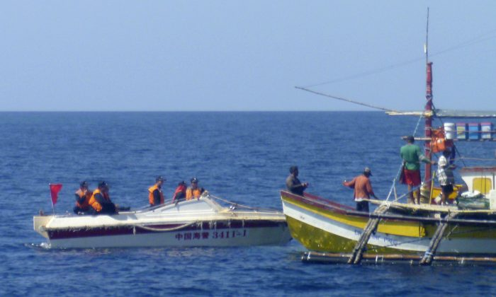 In this Feb. 27, 2015, photo, provided by Filipino fisherman Renato Etac, Chinese Coast Guard members approach Filipino fishermen near Scarborough Shoal in the South China Sea. An international tribunal has found that there is no legal basis for China's claiming rights to much of the South China Sea. The Permanent Court of Arbitration (PCA) issued its ruling Tuesday, July 12, 2016, in The Hague in response to an arbitration case brought by the Philippines against China regarding the South China Sea, saying that any historic rights to resources that China may have had were wiped out if they are incompatible with exclusive economic zones established under a U.N. treaty. (Renato Etac via AP)