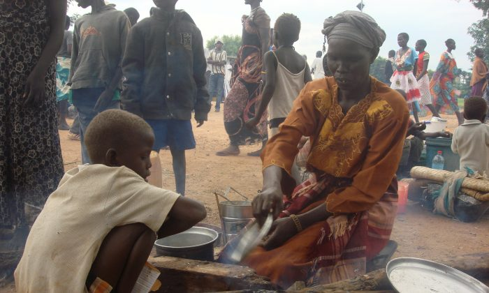 A woman prepares food as displaced women, men and children gather, in Juba, South Sudan at the UN compound in Tomping area on July 12, 2016. ( Beatrice Mategwa/UNMISS via AP)