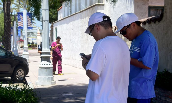 Brothers Jeffrey (L) and Stephen Wang check their cellphones as Tony Luu approaches, all playing Pokemon Go in San Gabriel, Calif., on July 13, 2016. (Frederic J. Brown/AFP/Getty Images)