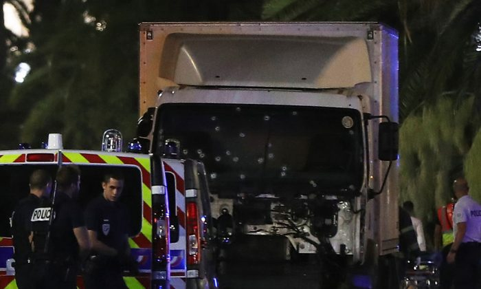 "Police officers stand near a van, with its windscreen riddled with bullets, that ploughed into a crowd leaving a fireworks display in the French Riviera town of Nice on July 14, 2016. Up to 30 people are feared dead and over 100 others were injured after a van drove into a crowd watching Bastille Day fireworks in the French resort of Nice on July 14, a local official told French television, describing it as a ""major criminal attack"". / AFP / VALERY HACHE        (Photo credit should read VALERY HACHE/AFP/Getty Images)"
