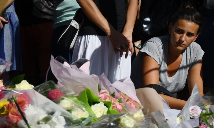 A woman at the makeshift memorial where people laid flowers to pay tribute to the victims the day after a man smashed a truck into a crowd of revelers celebrating Bastille Day, killing at least 84 people, on July 15, 2016. (ANNE-CHRISTINE POUJOULAT/AFP/Getty Images)