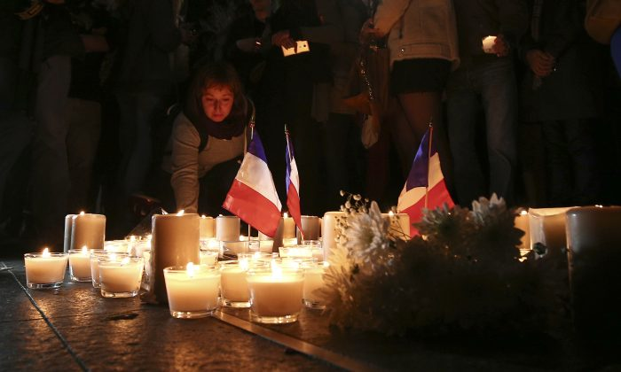 A woman places a candle during a vigil to honor victims of the Bastille Day tragedy in Nice, France, in Sydney, Australia, on July 15, 2016. (AP Photo/Rob Griffith)