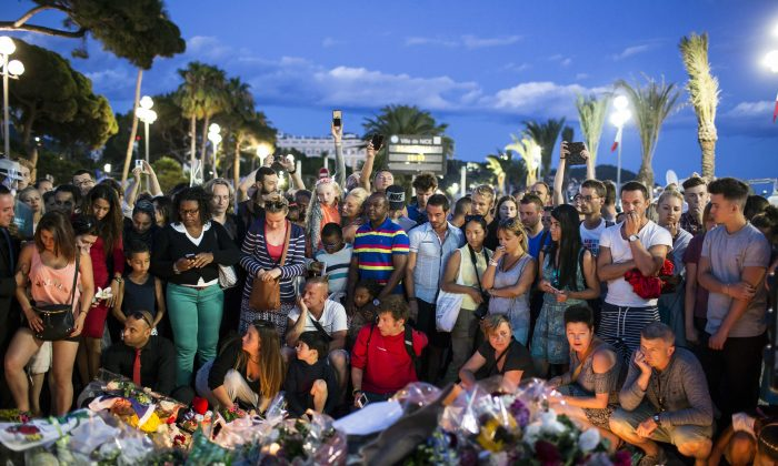 People gather at a makeshift memorial to honor the victims of an attack, near the area where a truck mowed through revelers in Nice, southern France, on July 15, 2016. (AP Photo/Laurent Cipriani)