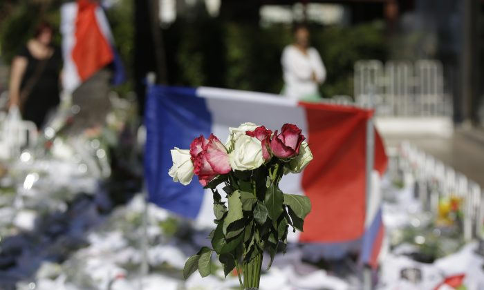 Floral and papers tributes are laid with a French flag near the scene of a truck attack in Nice, southern France, on July 16, 2016. (AP Photo/Luca Bruno)