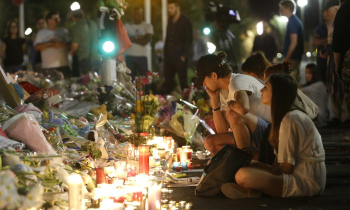 People gather at a makeshift memorial to honor the victims of an attack, near the area where a truck mowed through revelers in Nice, southern France, on July 16, 2016. (AP Photo/Claude Paris)