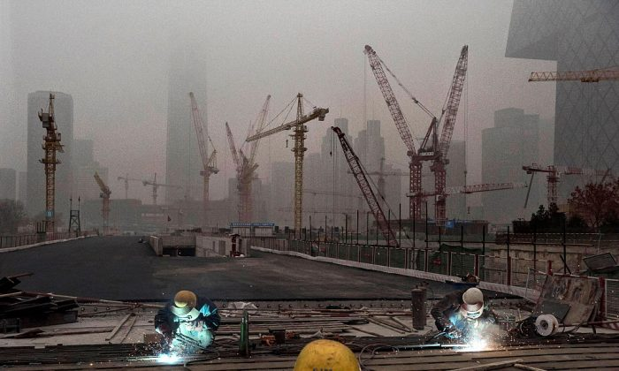 Chinese workers weld at a construction site in heavy pollution on Nov. 29, 2014 in Beijing. (Kevin Frayer/Getty Images)