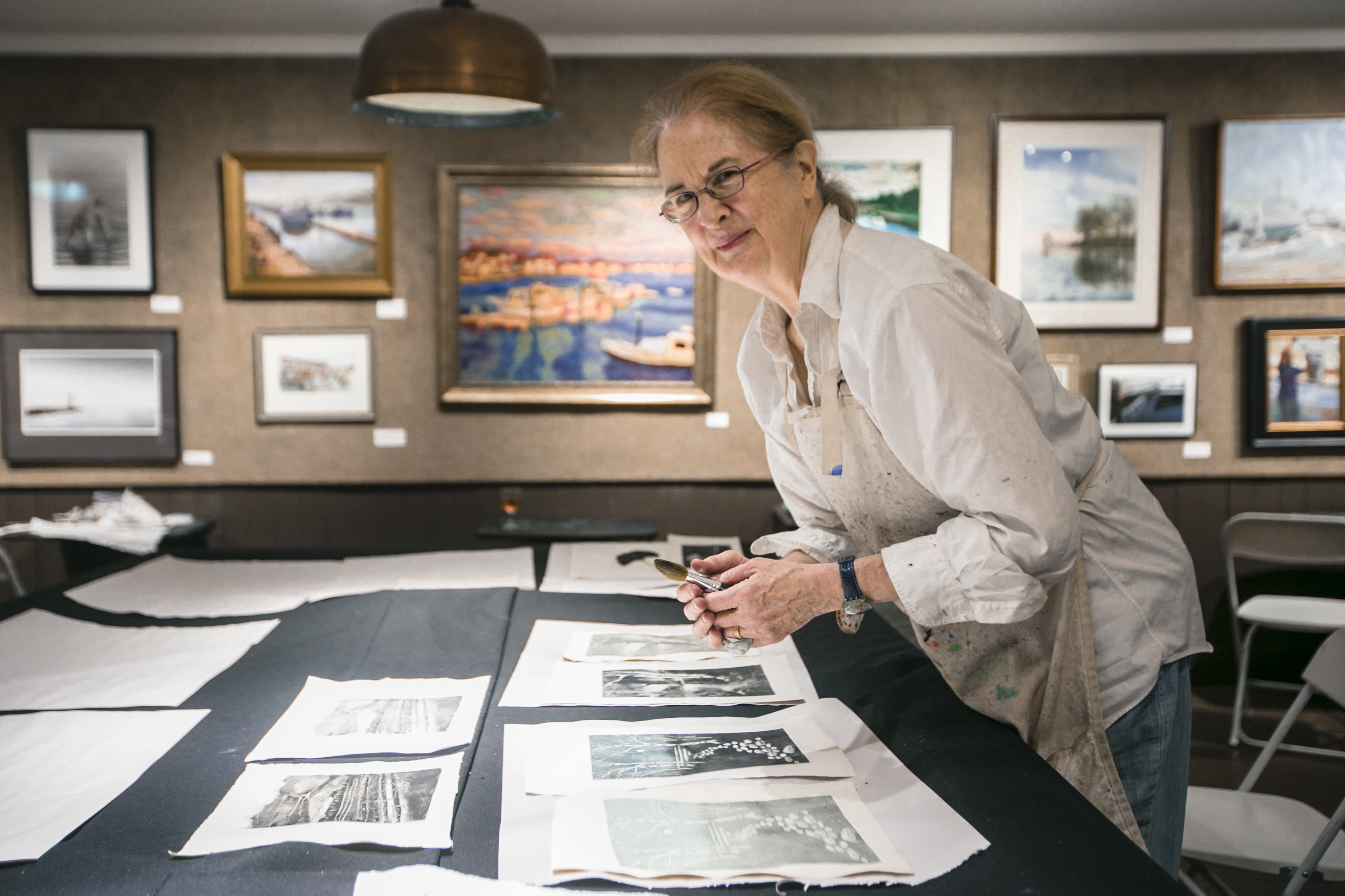 Annie Shaver-Crandell looks at her prints at the monotype party of the Salmagundi Club on July 12, 2016. (Samira Bouaou/Epoch Times)