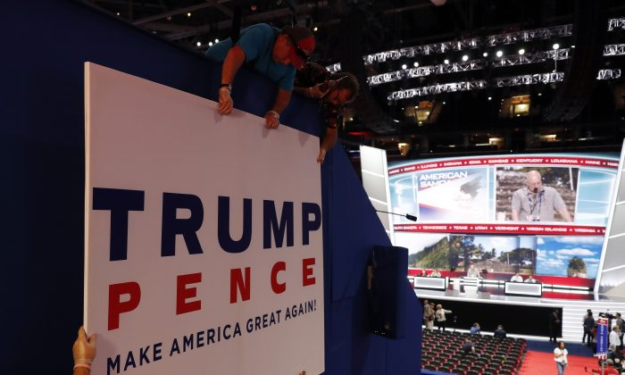 Workers place a sign as they prepare at Quicken Loans Arena for the Republican National Convention, Sunday, July 17, 2016, in Cleveland. (AP Photo/Carolyn Kaster)