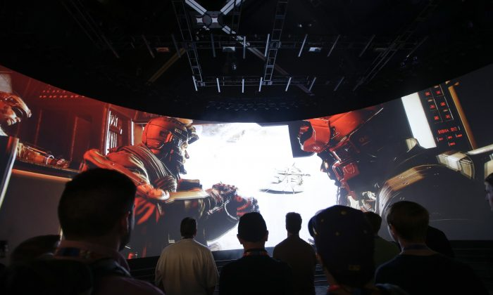 """People watch the """"Call of Duty: Advanced Warfare"""" video game trailer at the Activision booth at the Electronic Entertainment Expo in Los Angeles, Calif. on June 12, 2014. (AP Photo/Jae C. Hong)"""