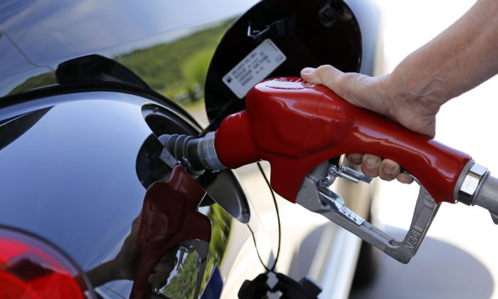 A customer re-fuels her car at a Costco in Robinson Township, Pa., in 2015.  The U.S. government says the fuel economy of the nation's fleet of cars and trucks likely won't meet its targets in 2025 because low gas prices have changed the types of vehicles people are buying. (AP Photo/Gene J. Puskar)