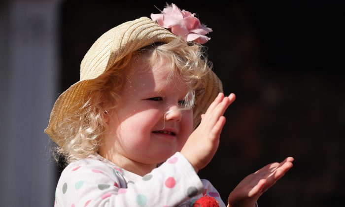 A young girl claps as she watches the colliery bands pass by during the annual Durham Miners Gala on July 11, 2015 in Durham, England. This is the 131st gala which brings together the communal values, culture and mining heritage of the north east of England. Thousands of people attend the event to listen to the brass bands, socialise and show their allegiance to the banners from the former colliery villages throughout the north.  (Photo by Ian Forsyth/Getty Images)