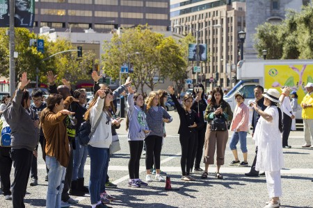 Passersby learn the Falun Gong exercises before the anti-persecution parade in San Francisco on July 16. (Epoch Times)