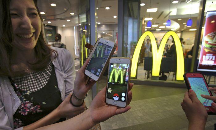 "Women play ""Pokemon Go"" in front of a McDonald's restaurant in Tokyo, Friday, July 22, 2016. (AP Photo/Koji Sasahara)"