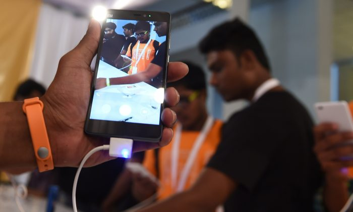 Xiaomi's Mi4i smart phone and Mi Band fitness tracker. Security weaknesses on many popular fitness trackers may allow hackers to access or potentially manipulate user data, a study showed.  (MONEY SHARMA/AFP/Getty Images)