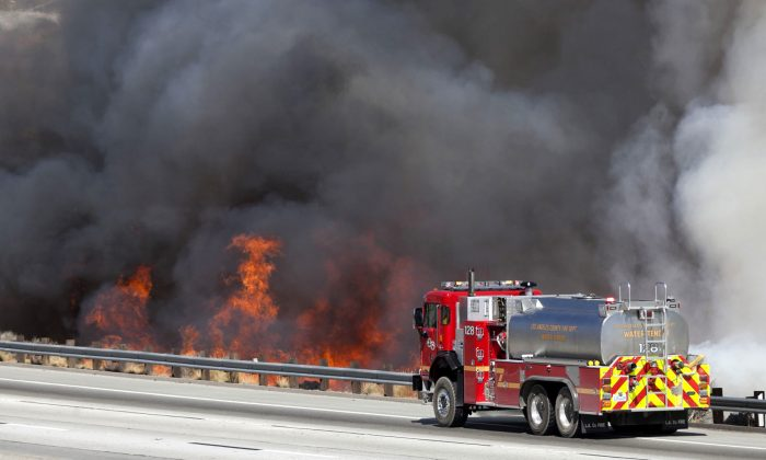A Los Angeles County Fire water tender fire truck sprays down flames as they near the northbound Highway 14 during the Sand Fire in Santa Clarita on July 22, 2016. (Katharine Lotze/The Santa Clarita Valley Signal via AP)