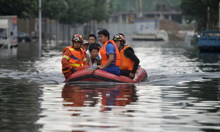 Rescuers use a raft to transport people along a flooded street in Shenyang in northeastern China's Liaoning Province on July 21, 2016. (Chinatopix Via AP)