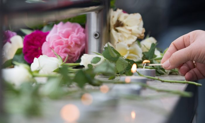 Candles are lit near a mall where a shooting took place leaving nine people dead in Munich, Germany, on July 23, 2016. (AP Photo/Sebastian Widmann)