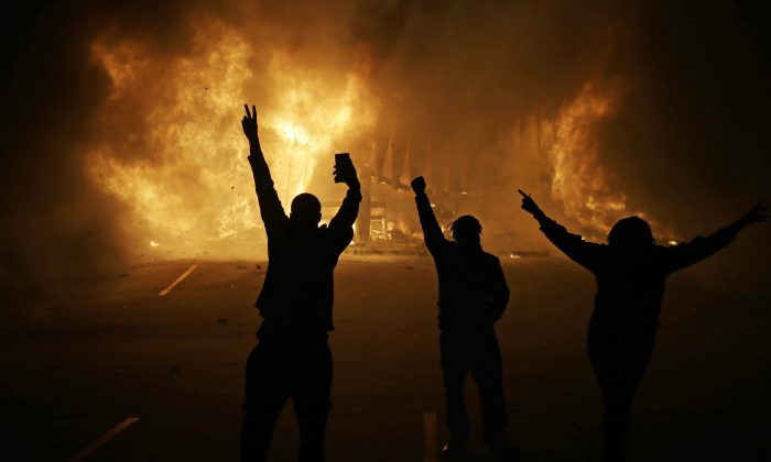 People watch as stores burn in Ferguson, Mo., on Nov. 25, 2014. (AP Photo/David Goldman)