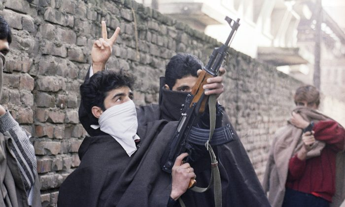 Young Muslim separatists brandish weapons on a street defying curfew and demanding independence in Kashmir, in Srinagar, India, on Jan. 23, 1990. (AP Photo/Ajit Kumar)
