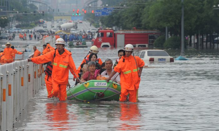 Fire workers transfer citizens with inflatable boat on flooded street in Taiyuan, China's Shanxi Province, on on July 20, 2016. (VCG via Getty Images)
