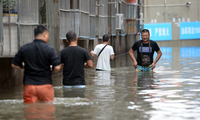 People making their way through a flooded area in Changping District in Beijing. Torrential rain lashing northern China in recent days has left 130 people dead in a province near Beijing. (STR/AFP/Getty Images)