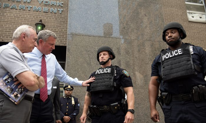 (L-R) NYPD Police Commissioner William Bratton and New York City Mayor Bill de Blasio inspect new NYPD equipment including helmets and vest during a press conference at the 84th Precinct in Brooklyn, New York, on Monday, July 25, 2016. (Demetrius Freeman/Mayoral Photography Office)