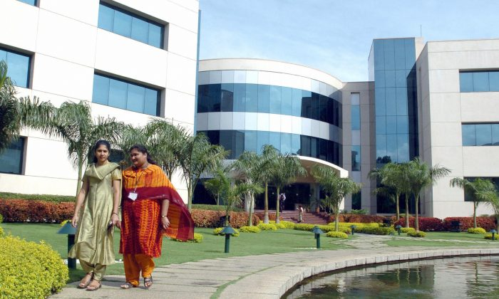 Employees of India software giant Infosys Technologies walk inside the company's compound in Bangalore on April 14, 2005. (Dibyangshu Sarkar/AFP/Getty Images)