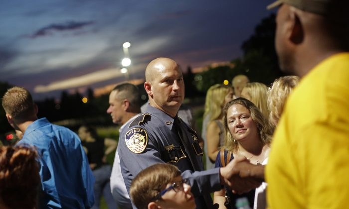 A police officer is greeted during a candlelight vigil for Baton Rouge Police Officer Matthew Gerald at Healing Place Church in Baton Rouge, La., on July 18, 2016. Gerald was one of three police officers killed by Gavin Long, who traveled from Kansas City, Mo., ambushing law enforcement officers along Airline Highway Sunday morning, July 17. (Joshua Lott/Getty Images)