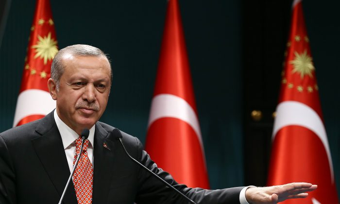 Turkish President Recep Tayyip Erdogan addresses people demonstrating against the failed military coup attempt in Turkey, via video conferencing at the Turkish Presidency in Ankara, Turkey, on July 24, 2016. (Yasin Bulbul/AFP/Getty Images)