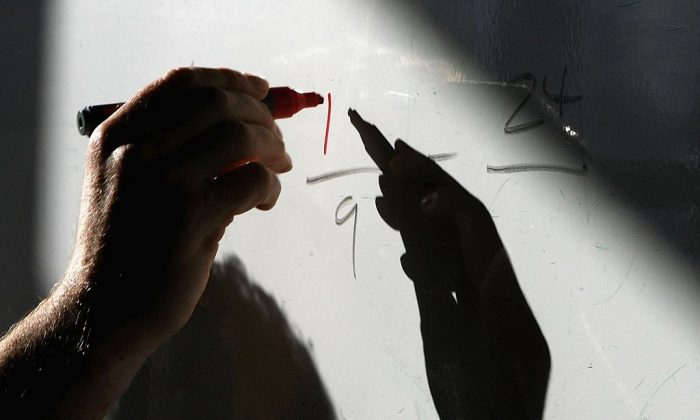 A math teacher writes on a white board in in this file photo. (Christopher Furlong/Getty Images)