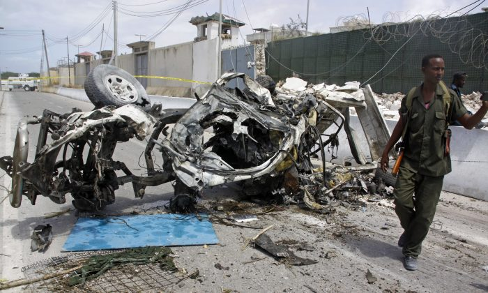 Somali soldier stand near the wreckage of a car bomb outside the UN's office in Mogadishu, Somalia, Tuesday, July 26, 2016. A suicide bomber detonated an explosives-laden car outside the United Nations Mine Action Service offices in Mogadishu, killing 13 people, including seven U.N. guards, a Somali police official said. (AP Photo/Farah Abdi Warsameh)