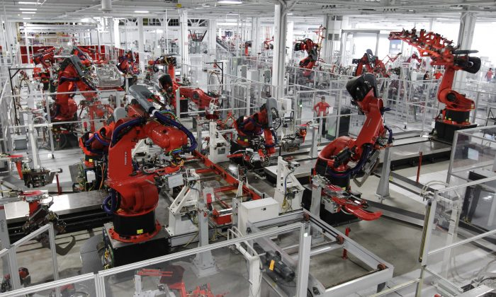Robots assemble a Tesla Model S at their factory in Fremont, Calif., on June 22, 2012.  (AP Photo/Paul Sakuma, File)