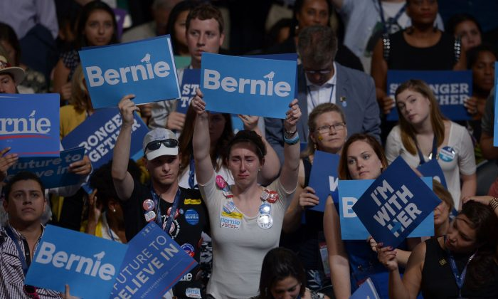 Supporters of Senator Bernie Sanders and Hillary Clinton hoist signs on Day 1 of the National Convention at the Wells Fargo Center in Philadelphia on July 25, 2016. (BRENDAN SMIALOWSKI/AFP/Getty Images)