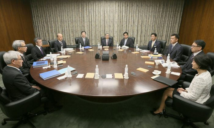 Governor of the Bank of Japan Haruhiko Kuroda, center back, poses with other members of Policy Board of the BOJ before their meeting at its headquarters in Tokyo Friday, July 29, 2016.  Japan's central bank has opted for a modest expansion of its lavish monetary stimulus to help perk up sluggish growth and combat deflation.  The Bank of Japan ended a policy meeting on Friday by announcing it will expand purchases of assets from financial institutions to help inject more cash into the economy and pursue its 2 percent inflation target. (Kyodo News via AP)