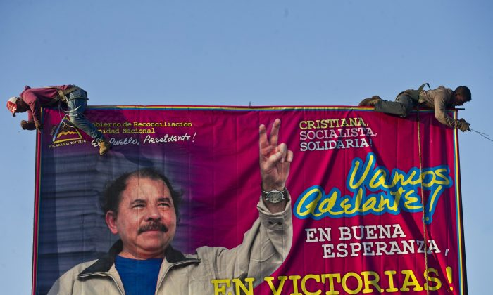 Workers install a billboard supporting Nicaragua's President Daniel Ortega along a street in Managua, Nicaragua, on Dec. 21, 2015. The opposition claims the presidential election in 2016 was a fraud as Ortega demonstrates many facets of a classic Latin American dictator. (AP Photo/Esteban Felix)