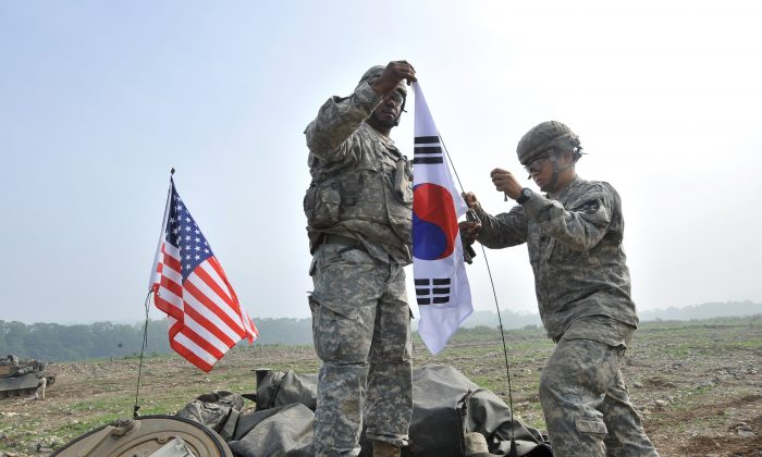 U.S. soldiers from 2nd Infantry Division hang a South Korean flag on the top of their M1A2 tank during a U.S.-South Korea joint river crossing exercise in the border city of Yeoncheon, northeast of Seoul, on May 30, 2013. (Jung Yeon-je/AFP/Getty Images)