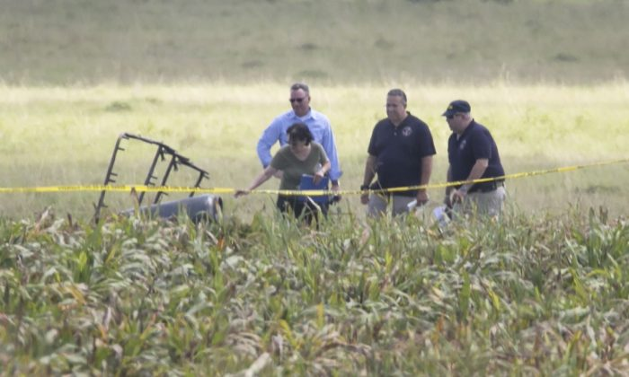 """The partial frame of a hot air balloon is visible above a crop field as investigators comb the wreckage of a crash Saturday, July 30, 2016, in Central Texas near Lockhart, Texas. Authorities say the accident caused a """"significant loss of life."""" (Ralph Barrera/Austin American-Statesman via AP)"""