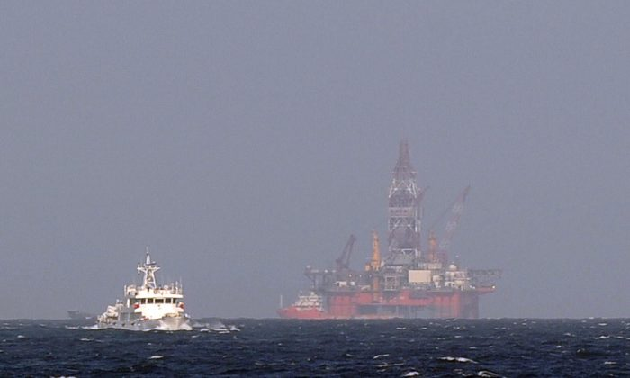 A Vietnamese coast guard ship moves toward a Chinese coast guard vessel near China's oil drilling rig in disputed waters in the South China Sea on May 14, 2014. (Hoang Dinh Nam/AFP/Getty Images)