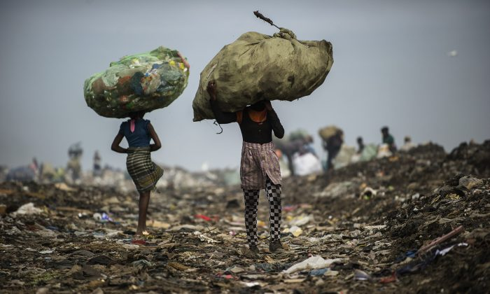 Girls carry bags of plastic items and tins as rubbish pickers sift through garbage at the Maputo municipal garbage dumping site in Maputo, Mozambique, on Oct. 14, 2014. (Gianluigi Guercia/AFP/Getty Images)
