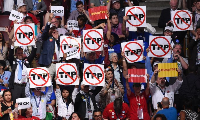 Delegates hold up anti-TPP signs during Day 1 of the Democratic National Convention at the Wells Fargo Center in Philadelphia, Pennsylvania, on July 25, 2016. (SAUL LOEB/AFP/Getty Images)