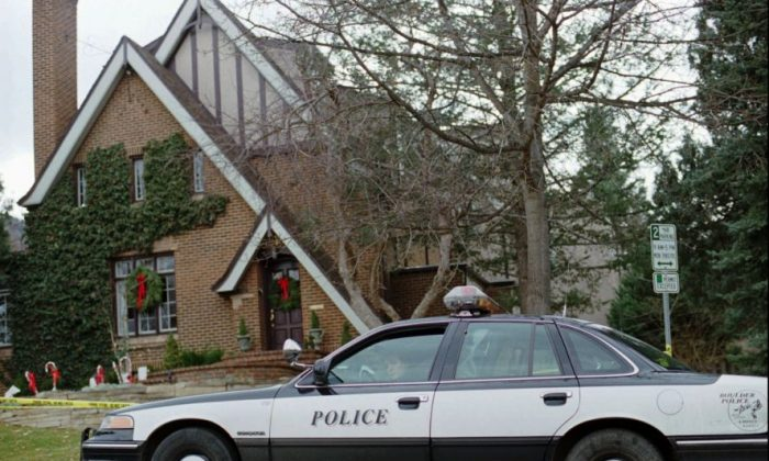 In this Jan. 3, 1997, file photo, a police officer sits in her cruiser outside the home in which 6-year-old JonBenet Ramsey was found murdered in Boulder, Colorado on Dec. 26, 1996. (AP Photo/David Zalubowski, File)