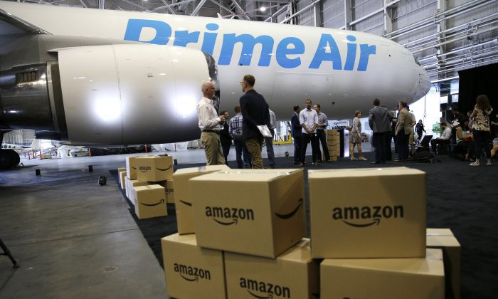 """Amazon.com boxes are shown stacked near a Boeing 767 Amazon """"Prime Air"""" cargo plane on display Thursday, Aug. 4, 2016, in a Boeing hangar in Seattle. (AP Photo/Ted S. Warren)"""